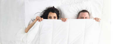 Top view of man and woman hiding under duvet. Happy funny couple laying together in bed. Lovely relationship in family. White bedding. Wake up and good morning concept Zdjęcie Seryjne