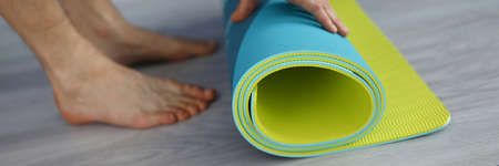 A man twists a mat for sports. Fitness at home. Rubber mat lies on the laminate