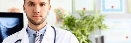 Portrait of smiling doctor with stethoscope standing at workplace in clinic. Medicine concept