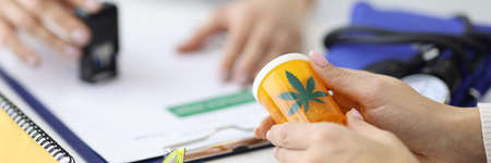 Patient holding jar of marijuana in hands. Doctor putting stamp on document. Legal purchase of narcotic drugs concept Standard-Bild