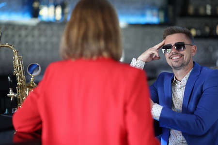 Smiling confident man in sunglasses meets woman near bar counter. Narcissistic personality disorder in men concept