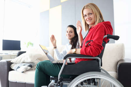 Woman in wheelchair with laptop on her lap waving in greeting with her girlfriend. Remote work for people with disabilities health concept