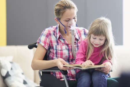 Woman with an oxygen mask and in wheelchair is reading book with little girl. Communication with loved ones in case of serious illnesses concept