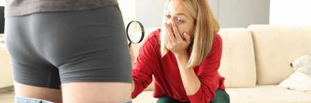 Man stands in shorts next to woman with magnifying glass, looking at her crotch in surprise. Male health examination and psychological problems in intimate life concept