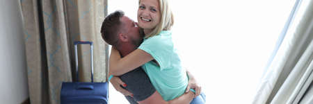 Man hold woman in his arms. Couple is happy arrive at hotel. Wife hug her husband neck, bent her knees.