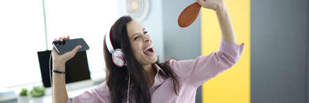 Woman in headphones on couch holds smartphone in her hands and pretends to sing. Emotional energy boost concept Stock fotó