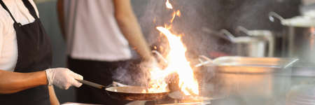 Cook in kitchen holds frying pan in which fire is burning. Cooking in restaurants and cafes concept