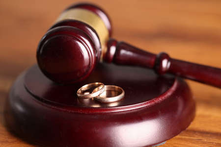 Closeup of judge hammer and wedding rings. Divorce proceedings concept