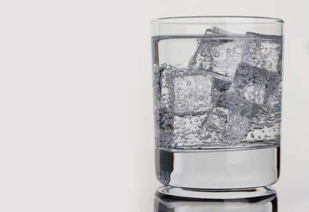 Closeup of glass with mineral water and ice. Quenching thirst concept