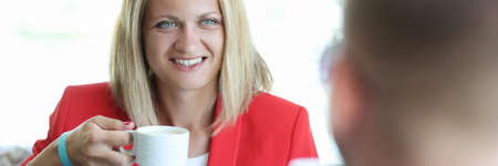 Smiling woman holding white cup and looking at man. Business meeting in cafe concept