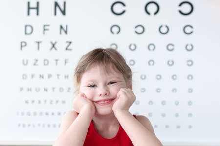Smiling little child against vision test table in medical clinic portrait. Health and happy childhood concept