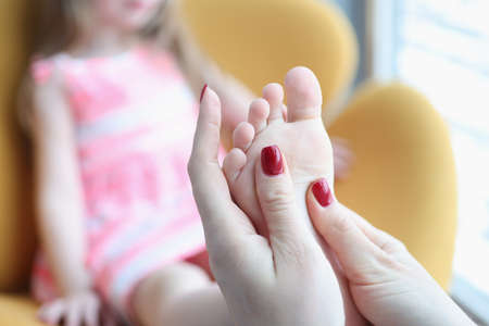 Little girl is given foot massage for flat feet