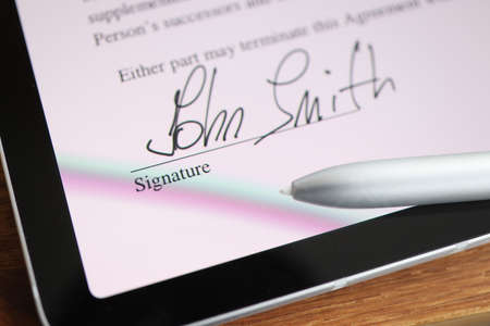 Stylus writing signature on digital tablet closeup