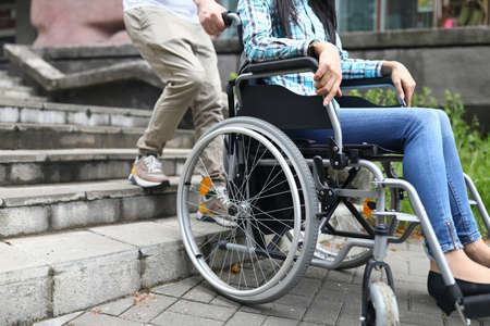 Man tries to drag wheelchair with woman onto stairs