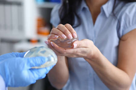 Doctor demonstrates silicone implants to women