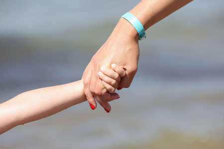 Woman hand holds child hand. Parental support for young children