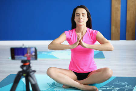 Woman in gym sits in lotus position in front of camera Reklamní fotografie