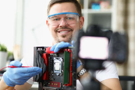 Blogger demonstrates on camera repair of computer board