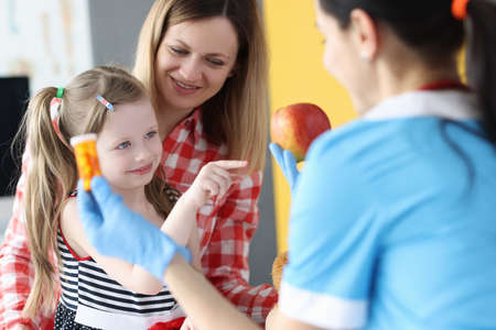 Doctor holding jar of medicine and apple in front of little girl and mother