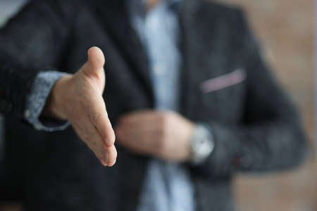Man in black jacket stretching out his hand for handshake closeup