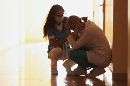 Tired doctors in protective medical mask sit on corridor Reklamní fotografie