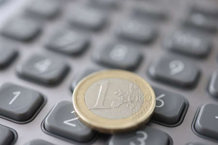 One euro coin is on calculator closeup Stock Photo