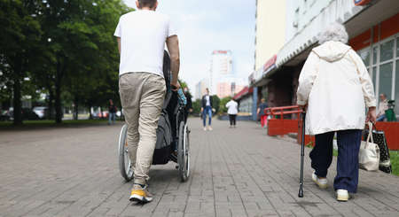 Man rolls a seated woman in wheelchair down street in city