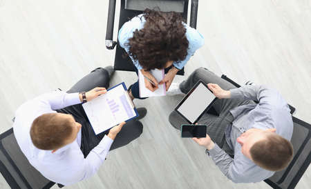 Business people sit on chairs with tablet and commercial business charts and discuss work plans top view