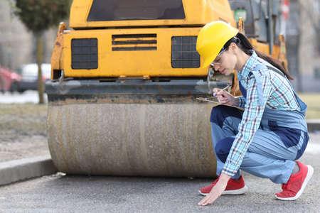 Woman examines asphalt pavement in front of asphalt paver