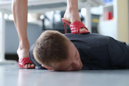 Business woman put heel on back of businessman closeup