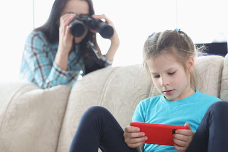Mom controls her daughter with phone through binoculars Archivio Fotografico