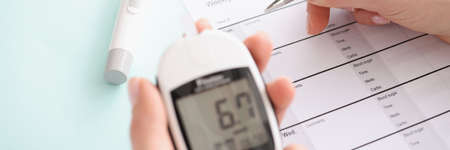 Glucometer with blood test results in patient hand fills in results in daily report