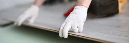 Gloved technician lays down laminate on backing Banque d'images