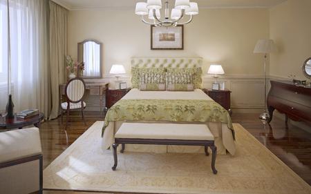 caoba: Dormitorio elegante estilo moderno. Dormitorio principal con paredes de moldeo de color crema, suave cama con una manta de oliva y cojines, muebles de caoba y alfombra estampada. 3D render Foto de archivo