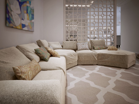 contemporary living room: Large corner sofa in a modern style. From fabric beige cushions. Arabic ornament. 3D render.