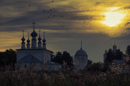 Sunset over the old christian churches: Saints Peter and Paul Church (left), Pokrovsky Cathedral (right). Taken in Suzdal, Russia Stock Photo