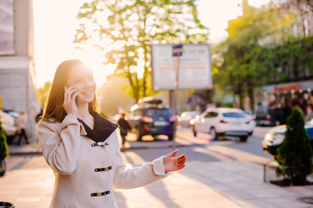 phone professional: young cheerful woman in city speaking on phone in sunset light