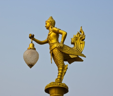 Golden light poles with traditional Thai angle sculpture in the park   photo
