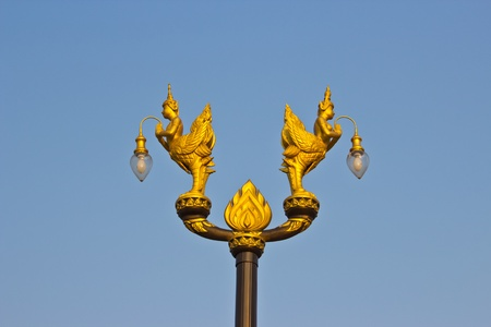 Golden light poles with traditional Thai angle sculpture in the park. photo