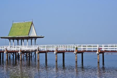 Wood bridge and wooden gazebo in the pool and blue sky photo