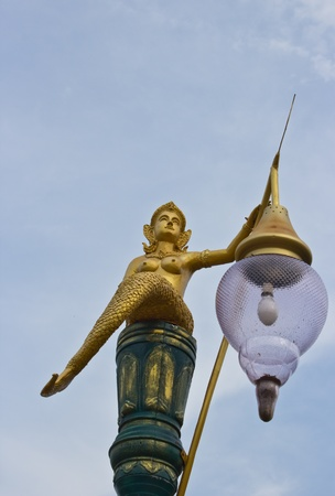 Golden mermaid light poles in the park and blue sky photo