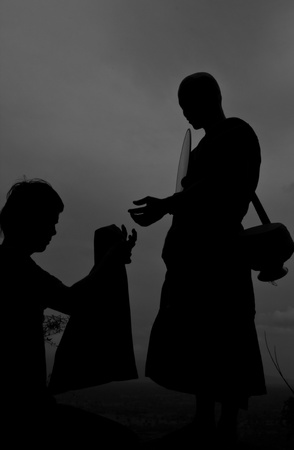 Buddhist monks on a cliff The silhouette  photo