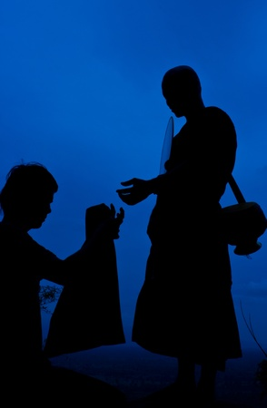 Buddhist monks on a cliff The silhouette  Stock Photo