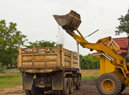 back hoe: Yellow bulldozer was scooping soil into the truck  in bad weather.