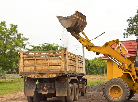 Yellow bulldozer was scooping soil into the truck  in bad weather Stock Photo - 14250517