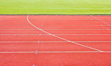 red running tracks with white start numbers at stadium closeup Stock Photo