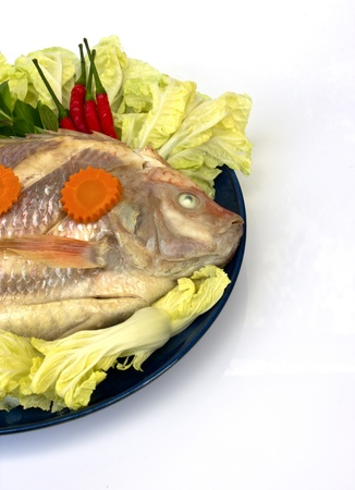 A Steamed Tilapia fish garnish with vegetables photo