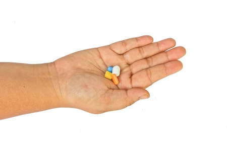 Pills in woman hand isolated on white background Stock Photo