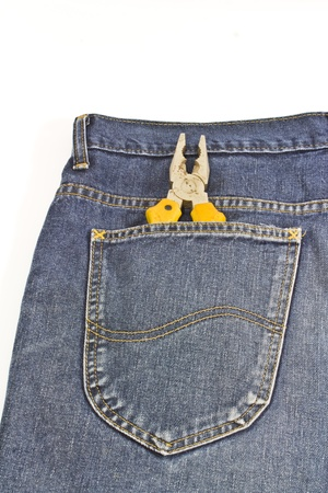 yellow pliers in pocket jeans on white photo