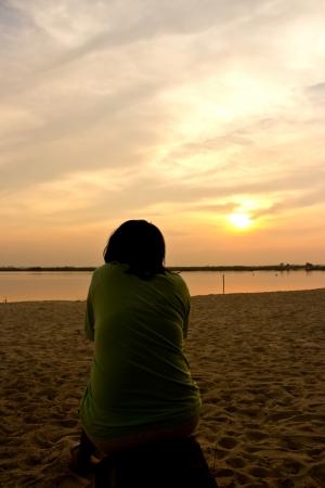 una mujer sola que se sienta en una playa de arena en frente de la puesta del sol Foto de archivo - 17174017